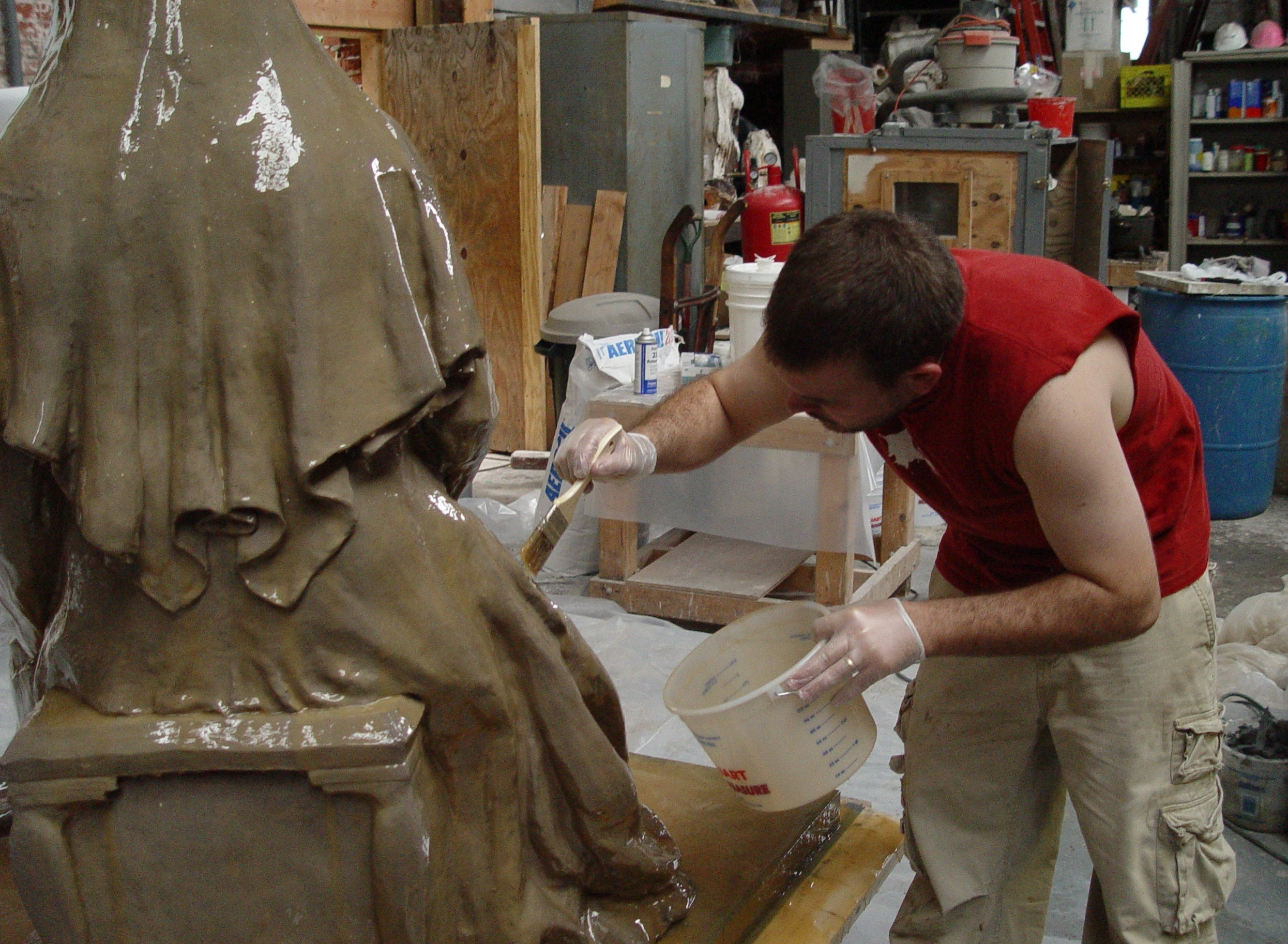 Zachary Kainz is applying the first coat of the rubber mold